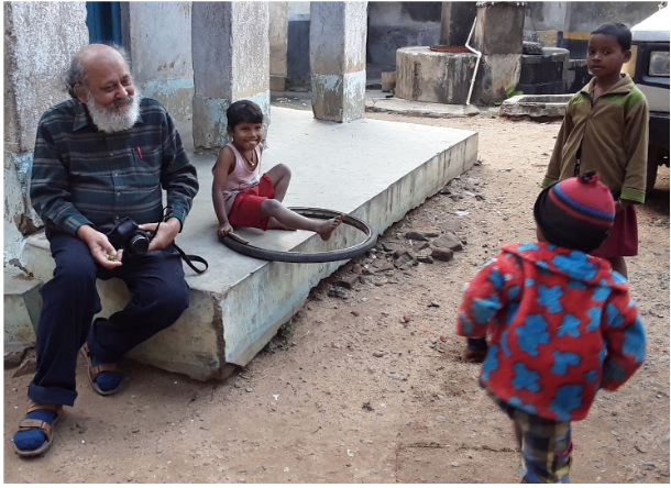 Ardhendu Chatterjee laughs with tribal kids in the village of Somenath Besra, West Bengal, India.