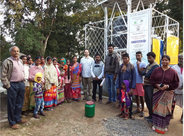 Standing with villagers and DRCSC staff in front of a water purification system whose waste water is feeding a thriving vegetable garden.